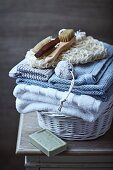Still-life arrangement of toiletries, bath towels and organic olive oil soap