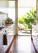 View from modern fitted kitchen onto terrace with sun lounger and palm trees
