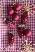 Red Christmas tree decorations and straw stars on gingham cloth