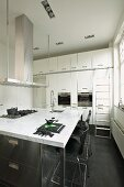 Kitchen island with marble worksurface in white fitted kitchen with black floor tiles