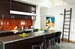 Dark brown designer kitchen with orange glass splashback, stainless steel worksurface on counter with bar stools