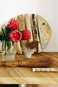Proteas in vase and rustic hand brush on table in front of wooden fish sculpture leaning against wall