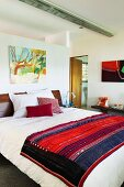 Ethnic blanket on double bed in modern bedroom