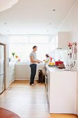 Man, child and dog in white kitchen