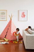 Children playing in front of red and white striped teepee on parquet floor in living room