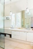 Bright bathroom with towel compartment and cupboard doors in masonry washstand below small pendant lamps