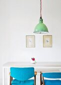 Hand-crafted dining table and chairs with blue upholstery below vintage pendant lamp in front of framed postcards on wall