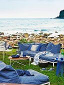 Casual outdoor furniture with metal frames and blue-covered cushions on stony sea shore