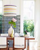 Protea flower in vase on dining table and chairs with white, upholstered backs below pendant lamp with striped lampshade