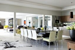 Long dining table with upholstered chairs in front of elegant kitchen; seating area with sofa combination in background in large, open-plan interior