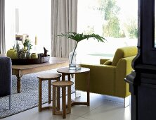 Pale wood side tables next to lime green armchair and tray of vases and ornaments on wide coffee table