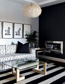 Black and white, Scandinavian-style seating area; sofa and glass table on rug with wide stripes in front of chimney breast painted anthracite grey