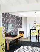Floral patterns on wallpaper, lime-green fabrics and dark grey structured rug of home studio; chandelier above staircase in background
