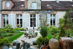 Jugs, stoneware and earthenware containers for sale on a gravel path in the garden of an old French country house