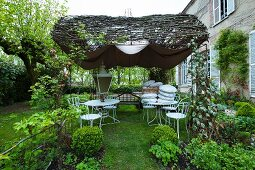 A sales exhibition of white metal furniture under a sunshade in the garden of a French country house