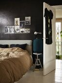 Bed with upholstered headboard below photos tacked on black-painted wall next to open interior door
