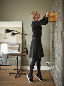 Young woman rummaging in drawer of old filing cabinet in front of table with industrial-style, vintage clip lamps