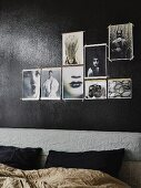 Bed with upholstered headboard below photos tacked to black-painted wall