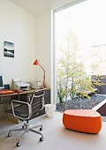 Classic office chair with black leather seat and orange, designer pouffe in home office; glass wall facing courtyard with birch trees in gravel bed