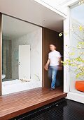 View from courtyard with wooden platform through frameless glass wall into white bathroom opposite home office; blurred man walking between the rooms
