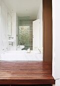 View from courtyard with wooden platform through frameless glass wall into bathroom
