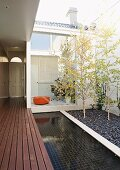 Entrance to courtyard of house with separate home office; purist design with wooden platform, pool and birches in gravel bed
