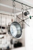 Retro metal colander and kitchen utensils hanging from rod below ceiling