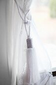 Classic, white cord tieback with tassel on curtain at window