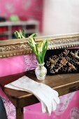 White lady's gloves and small, crystal vase of spring flowers on console table below mirror