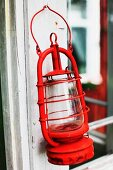 Old, red hurricane lamp hanging from white window frame