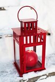 Rote kugelförmige Kerze in roter Laterne auf verschneiter Holztreppe