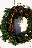 An Haustür aufgehängter Adventskranz mit roten Beeren