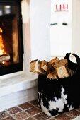 Holzscheite in Felltasche neben gemauertem Kamin mit Feuer
