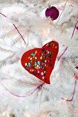 Rotes gebasteltes Herz mit bunten Pailletten und violette Kugel an weißem, künstlichem Weihnachtsbaum