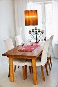 Mit Weingläsern und schmiedeeisernem Kerzenleuchter gedeckter Esstisch, stoffbespannte Retroleuchte und Holzstühle mit Hussen