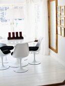 Tulip-Stühle an rundem Tisch mit Adventskerzen; Goldrahmenspiegel an der Wand