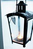 Lit tealight in black lantern