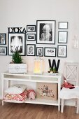 White console table below black and white photos in black frames on wall