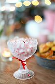 Sweets in retro glass bowl with red ribbon on wooden table