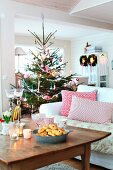 Scatter cushions on white sofa, rustic wooden coffee table and decorated Christmas tree in rustic living room