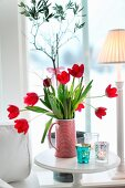 Red and white striped jug of red tulips on side table next to window
