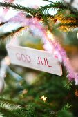 Small wooden sign with Christmas greetings hanging on fir tree