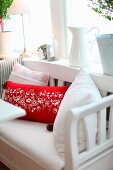 Red and white cushions on rustic wooden bench below window