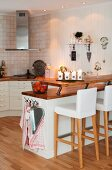 Upholstered bar stools at counter in open-plan, country-house kitchen
