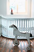 Vintage, white, wooden, three-wheeled horse in front of carved wooden balustrades painted white