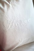 White cushion cover embroidered with lettering