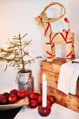 Festive arrangement of red apples and candle stuck in apple in front of straw reindeer decorated with red ribbons on wooden trunk in corner