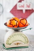 Oranges stuck with cloves in star and heart-shaped motifs on retro kitchen scales