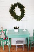 Wooden table and chairs painted pastel turquoise below wreath of fir branches on white wooden wall