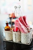 Apothecary's bottle, Christmas bauble and napkins in white containers in vintage bottle basket